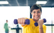 Young girl exercising with dumbbells in the gym.