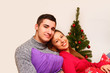 Smiling boy and girl with pillows and a Christmas tree isolated