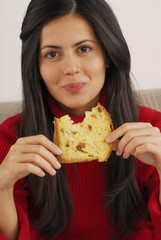 Joven mujer comiendo panetone,pan de navidad.