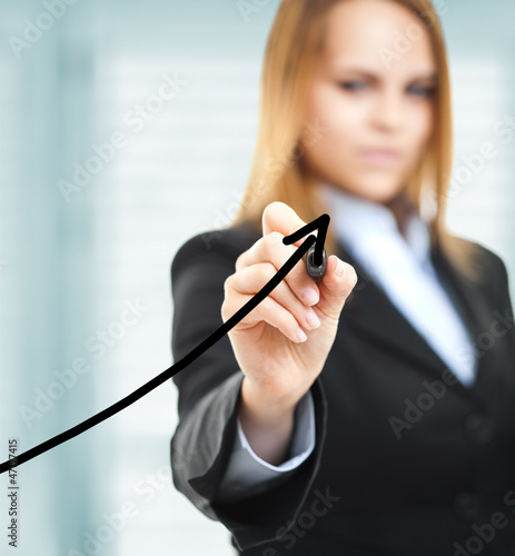 Businesswoman drawing a growing business graph