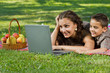 mom and child with  laptop outdoors