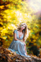 Lovely young lady wearing elegant white dress in the woods