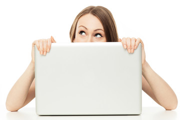 Woman looking out from behind a laptop