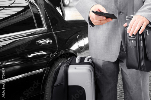 Traveling Businessman with His Luggage Using Phone