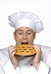 Cocinero chef sujetando un pastel de chocolate.