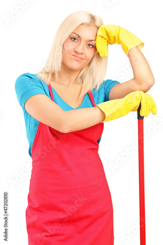 Exhausted female cleaner posing with brush