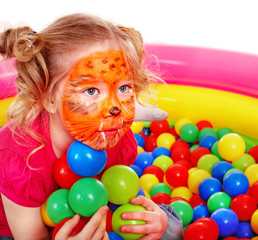 Little girl play colourful balls.