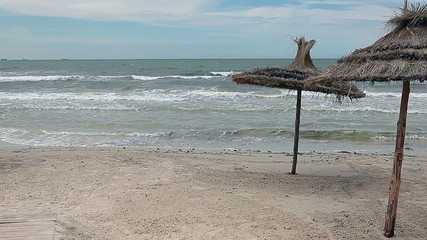Storm the Mediterranean Sea and palm-leaf parasols on the beach