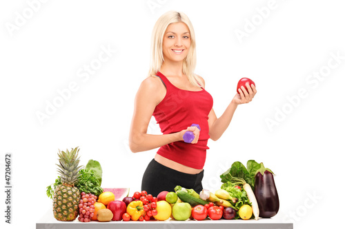 Female athlete holding a dumbbell and apple behind a pile of foo