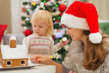 Mother showing baby Christmas Gingerbread House
