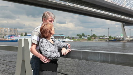 Loving mature couple standing on embankment together