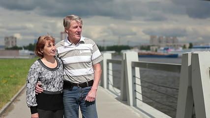 Elderly couple walking along the embankment, going to parapet