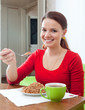 Happy girl  eats buckwheat  at home