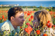 beautiful couple young women and young man in flowers, sea