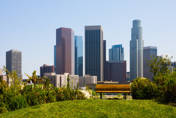 Skyscrapers in  Los Angeles with a bench in a foreground
