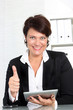 Businesswoman with tablet giving thumbs up