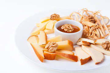 a plate with slices of cheese of different varieties
