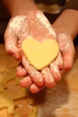 Plätzchen, Kekse backen mit Herz in Kinder-Hand