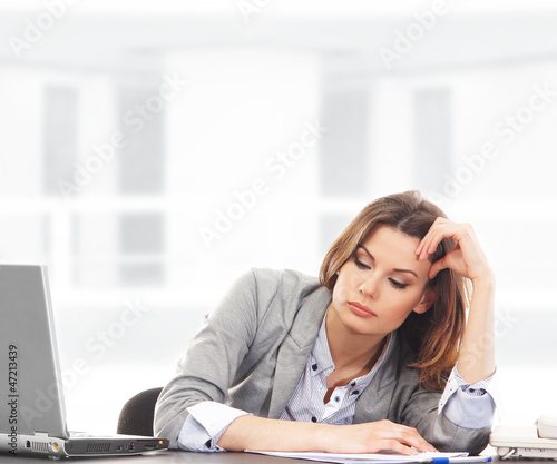 A young brunette businesswoman feeling tired on the work