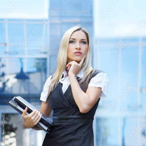 A young blond businesswoman thinking about her work