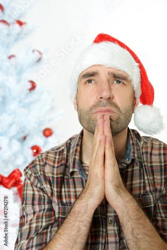 Mann mit Nikolausmütze betet