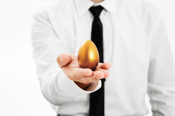 Golden egg in hand businessman
