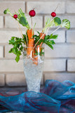 Carrot and berries ikebana decorations in a glass vase.
