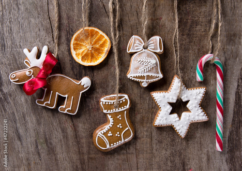 Traditional gingerbread cookies hanging over wooden background
