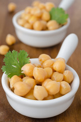 Two cups of boiled chickpeas on a wooden background close up