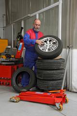 garagiste soulevant pneu de voiture