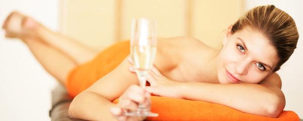 Blondine auf der Massageliege mit Sektglas