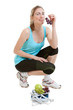 Sporty young woman with scales and fruits. healthy lifestyle