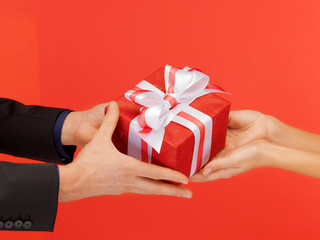man and woman's hands with gift box