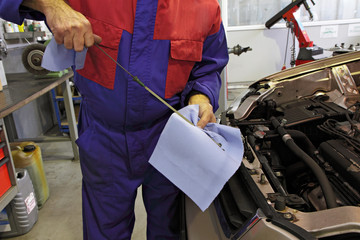 garagiste vérifiant niveau d'huile moteur
