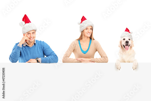 Smiling couple and dog with santa hats posing behind a panel
