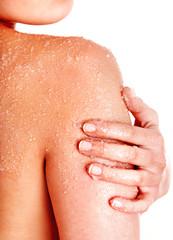 Beautiful young woman scrubbing body.