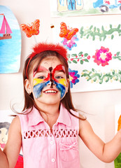 Child with  face painting in play room.