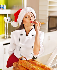 Female chef in Santa hat  holding  food.