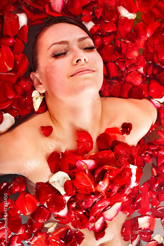Beautiful young woman in rose petal swim water.