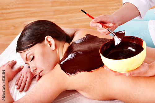 Woman having chocolate facial mask apply by beautician.