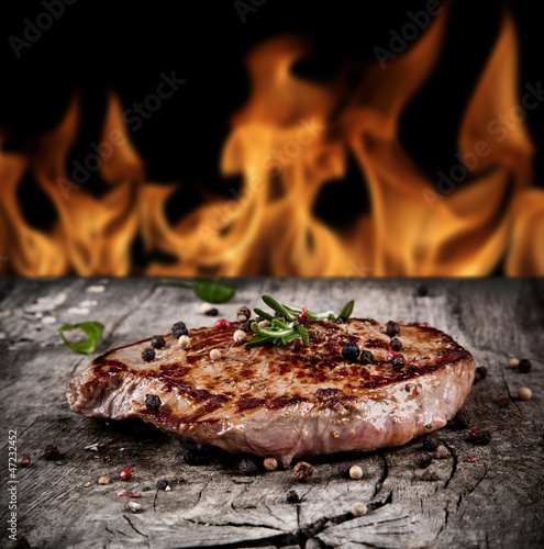 Delicious beef steak on wood with flames on backgrouns
