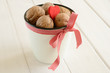 Walnuts in white bucket bounded up in red ribbon and bow