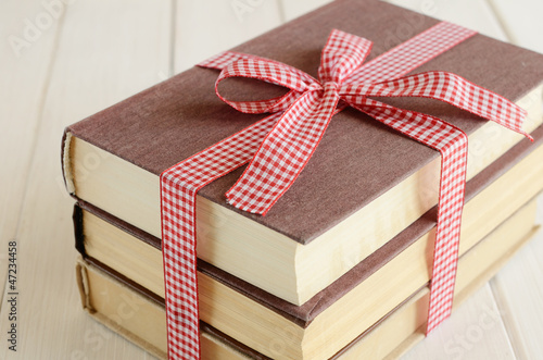 Books bounded up in red ribbon