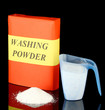 Box of washing powder with blue measuring cup, isolated on