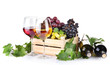 bottles and glasses of wine and assortment of grapes in wooden