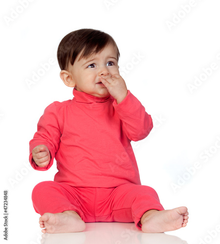 Scared baby girl with her hand in mouth sitting