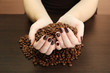 female hands with coffee beans, on wooden background