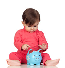 Adorable baby girl sitting with a blue piggy-bank