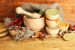 mortar, bowls and spoons with spices, on wooden background
