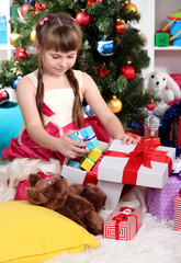 Beautiful little girl is happy gift in festively decorated room
